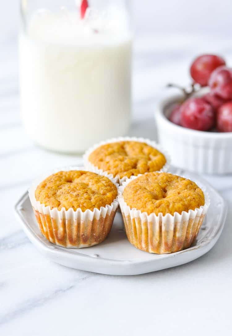 A photo of three healthy pumpkin muffins on a small white plate with a glass of milk in the background