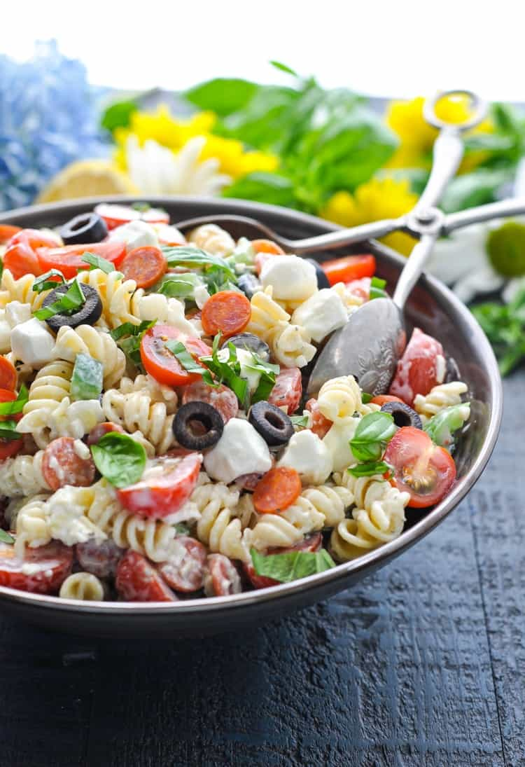 A side shot of a creamy Italian pasta salad in a large serving bowl