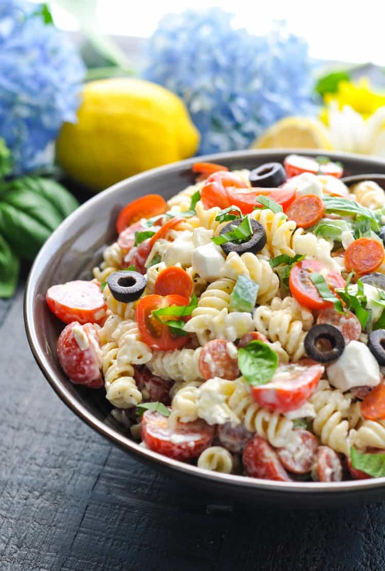 An side shot of a creamy Italian pasta salad topped with olives, tomatoes and cheese