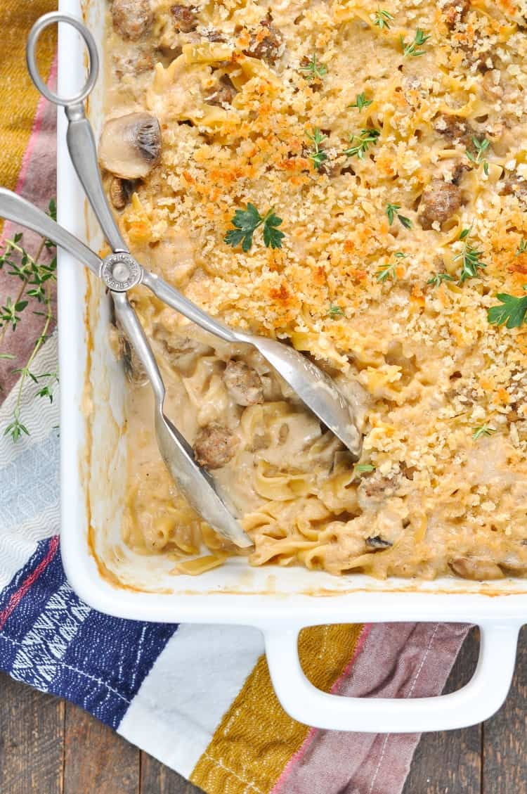 An overhead shot of a beef stroganoff casserole with serving spoons