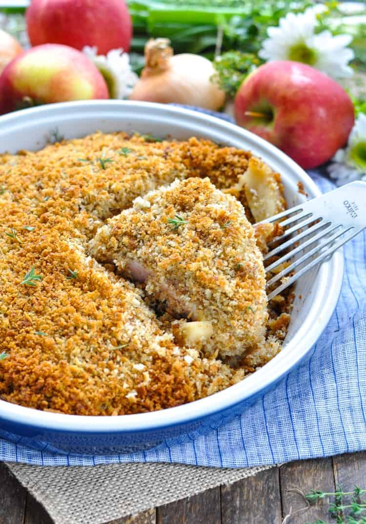 Boneless pork chops in a baking dish with apples and stuffing