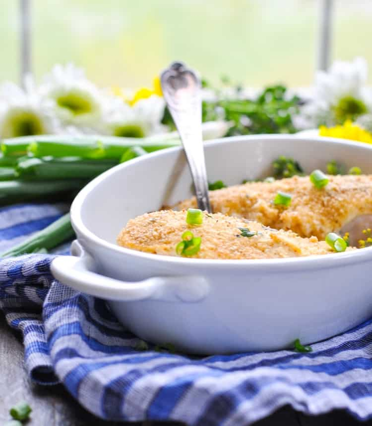 A side shot of parmesan smothered chicken in a white dish