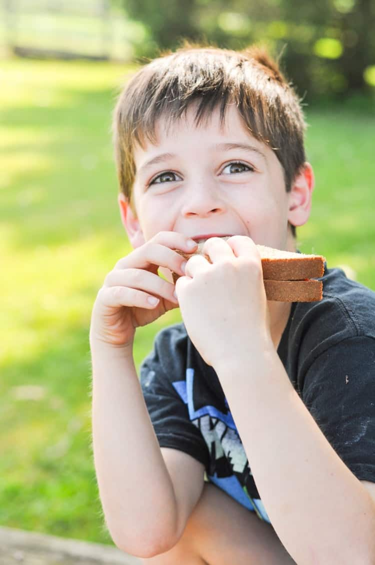 A boy eating a peanut butter and jelly sandwich