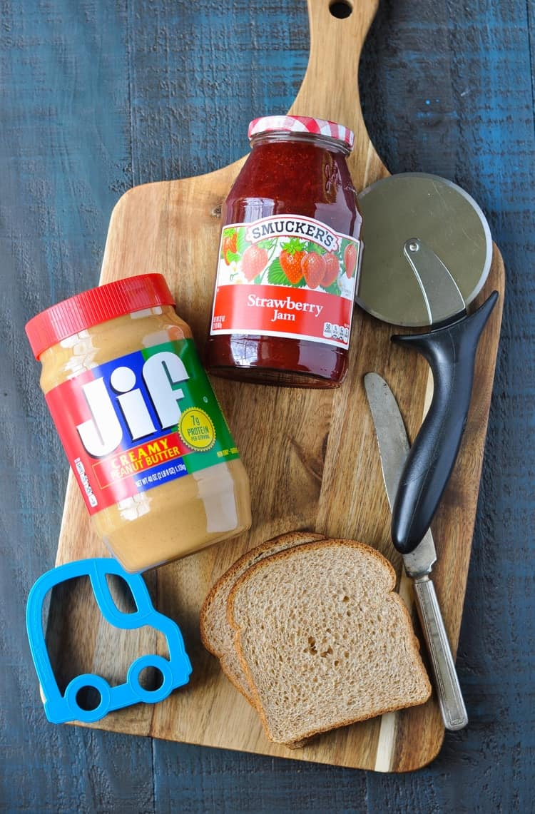 An overhead shot of peanut butter and jelly on a chopping board with slices of bread