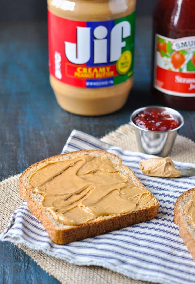 A close up shot of peanut butter spread on a slice of bread to make a peanut butter and jelly sandwich