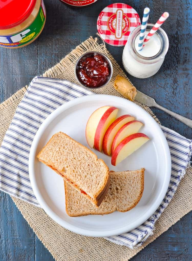 A peanut butter and jelly sandwich on a plate with some sliced apple