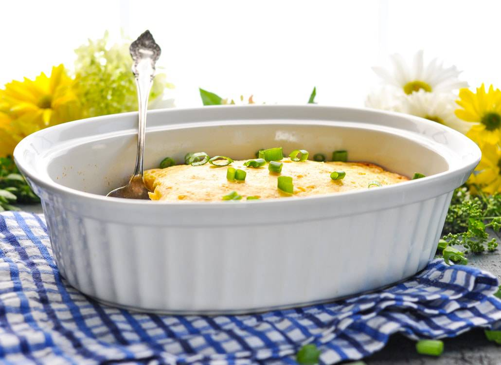 A side shot of corn pudding in a white dish with a spoon