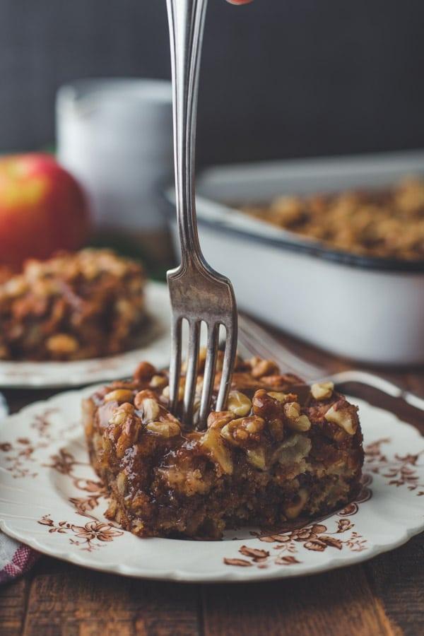 Fork taking a bite of apple walnut cake with glaze