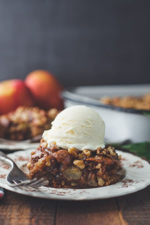 Scoop of vanilla ice cream on a slice of caramel apple walnut cake