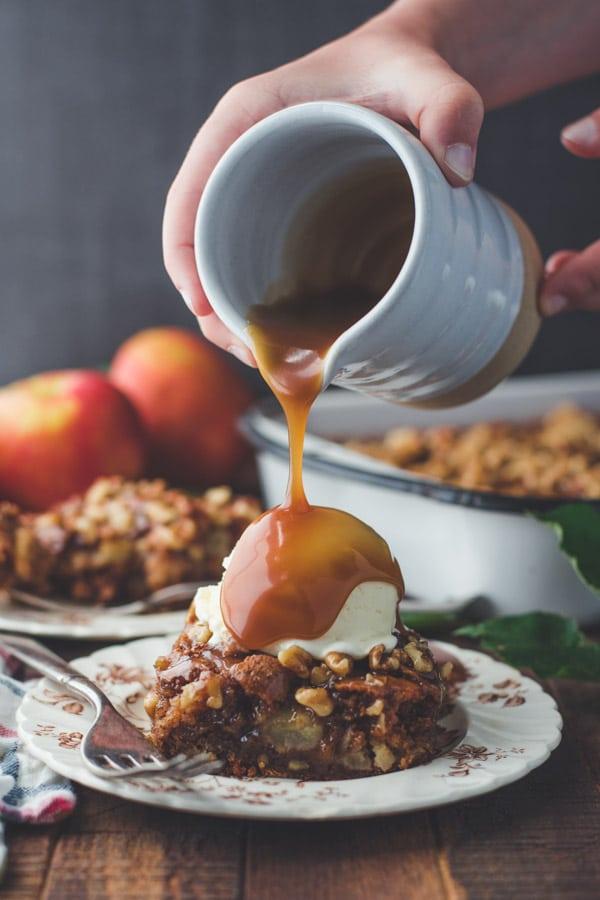 Pouring caramel glaze over vanilla ice cream and apple walnut cake