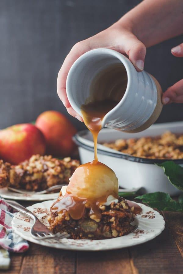 Pouring caramel glaze on top of vanilla ice cream and apple walnut cake