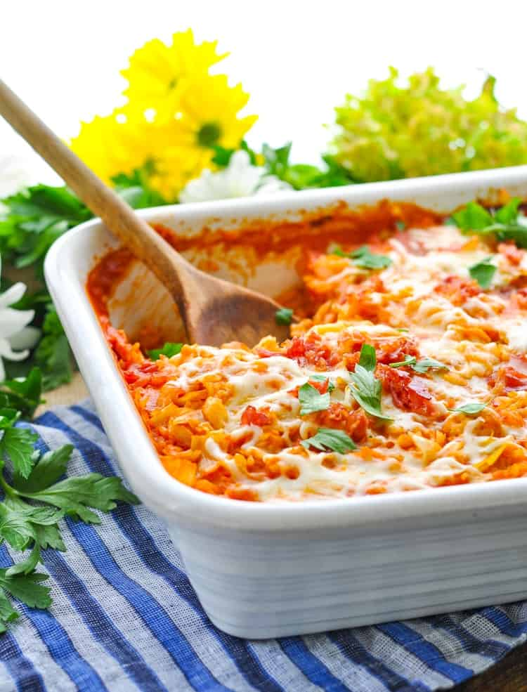 A close up of a stuffed cabbage casserole in a white casserole dish topped with herbs