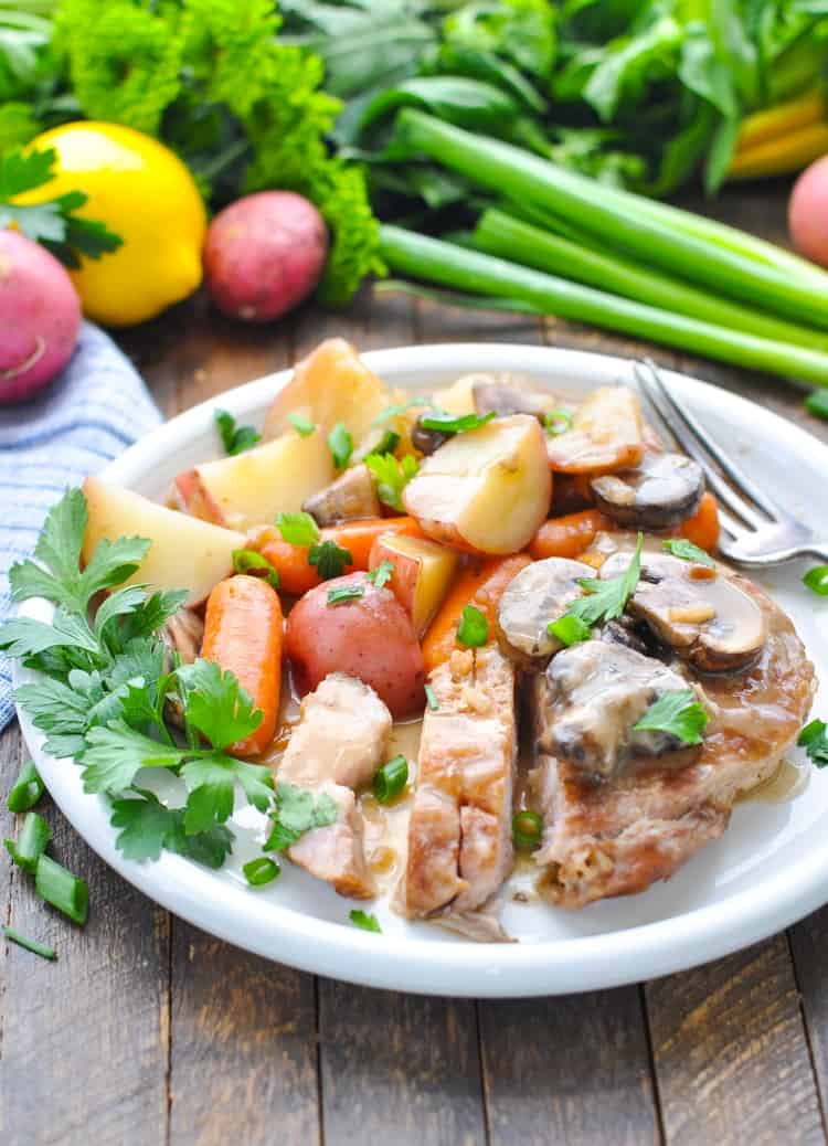 Slow cooker pork chops on a plate with potatoes, veggies and gravy