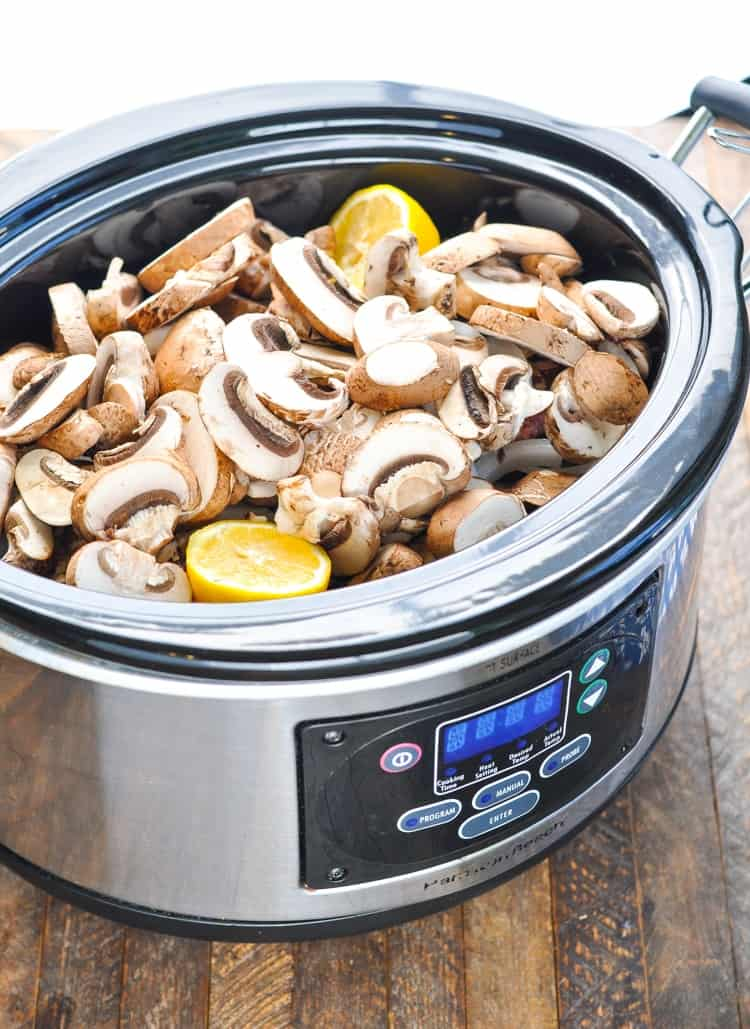 Slow cooker pork chops on a slow cooker topped with mushrooms and lemon