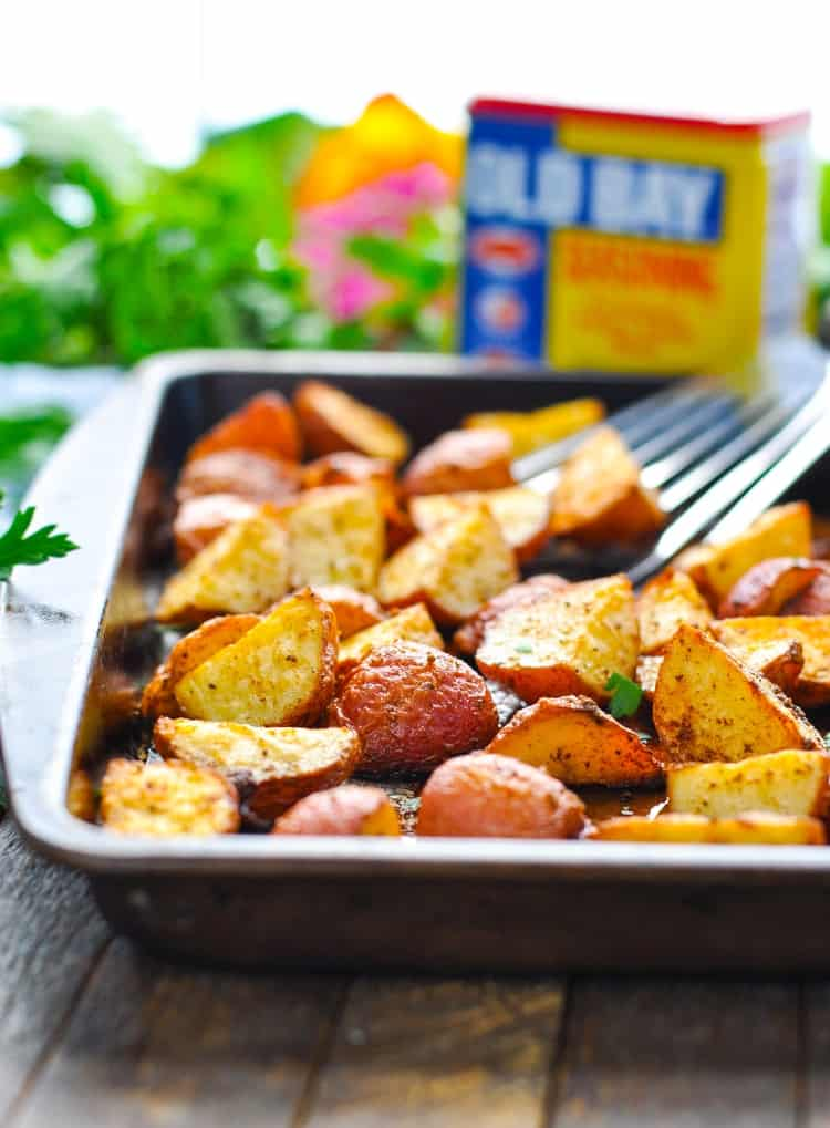 A close up of crispy seasoned red potatoes in a baking tray with a spatula