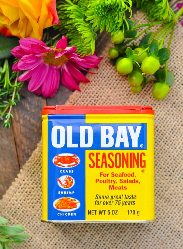 An overhead shot of Old Bay seasoning sitting on a wooden surface with flowers in the background