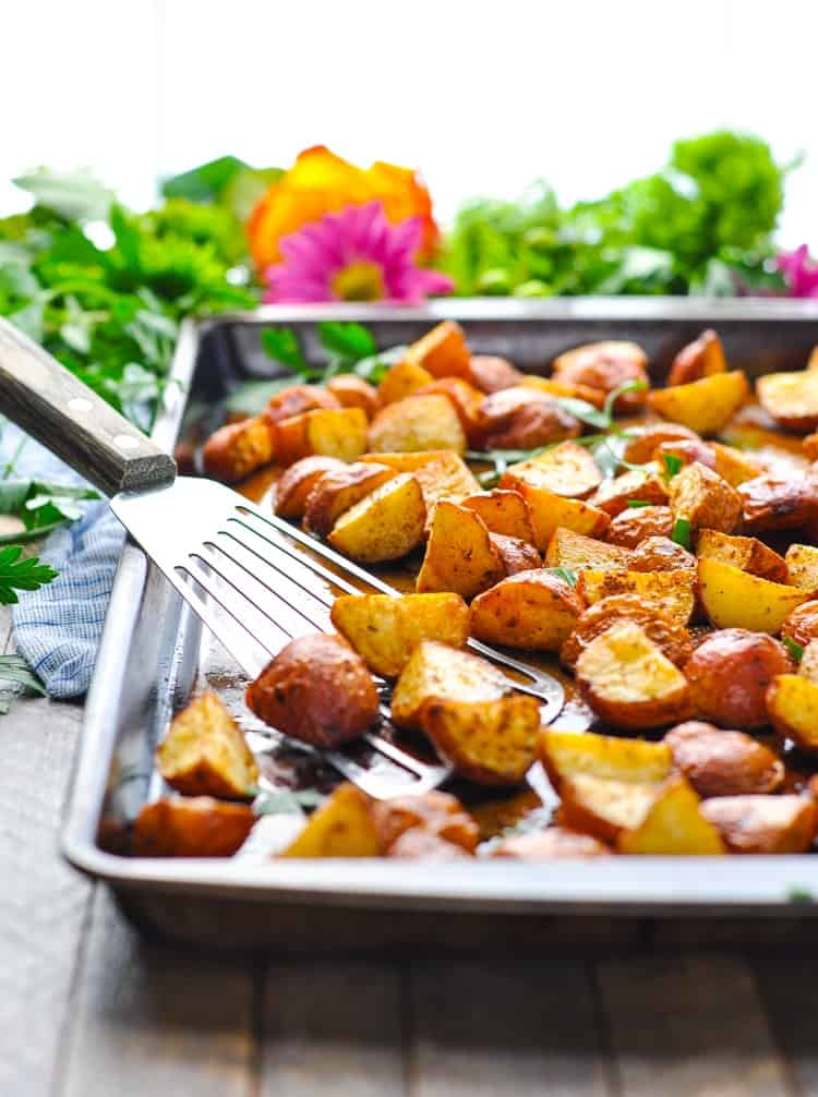 Crispy seasoned red potatoes in a tray and a spatula picking some up