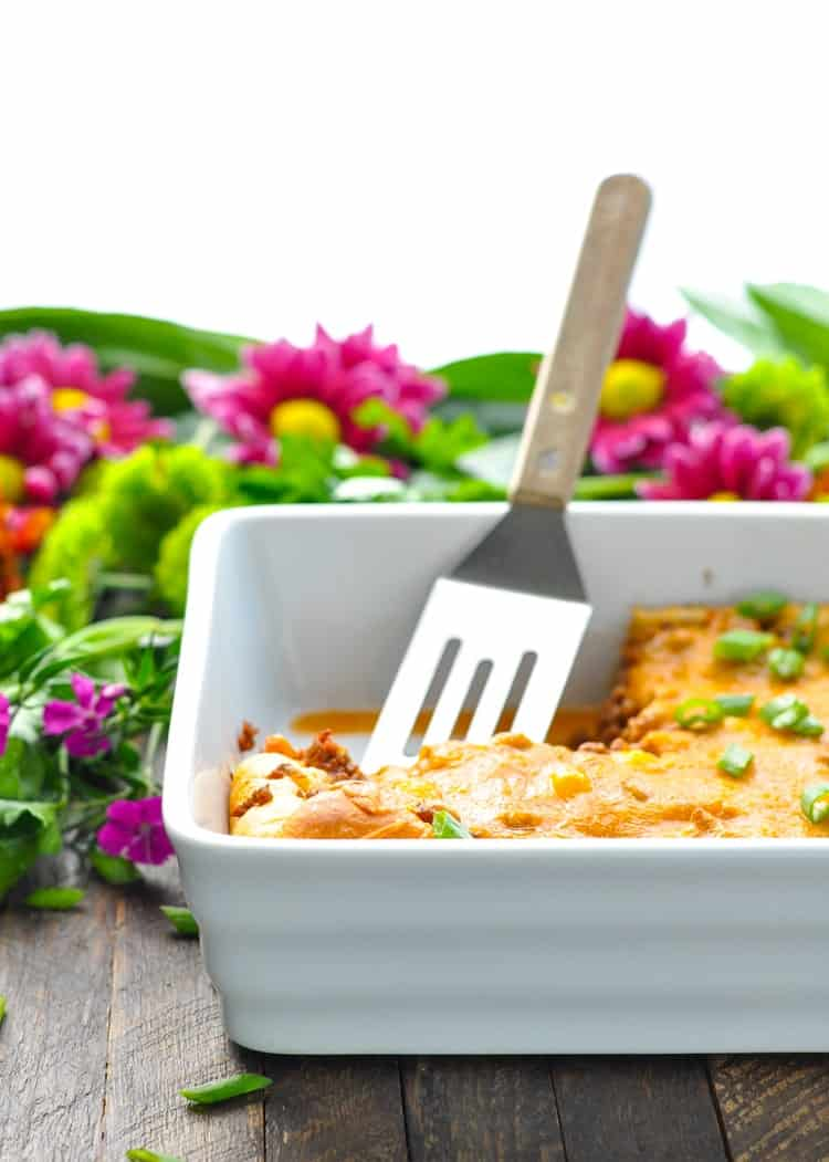 Ground beef casserole in a white dish with a spatula