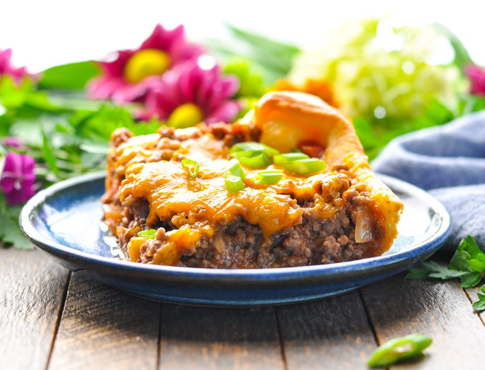 A slice of ground beef casserole on a blue plate topped with green onions