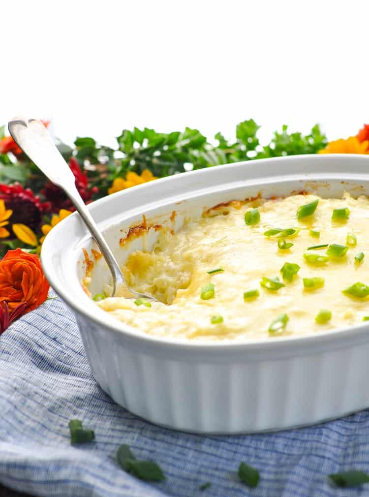A side shot of a cheesy potato casserole topped with green onions