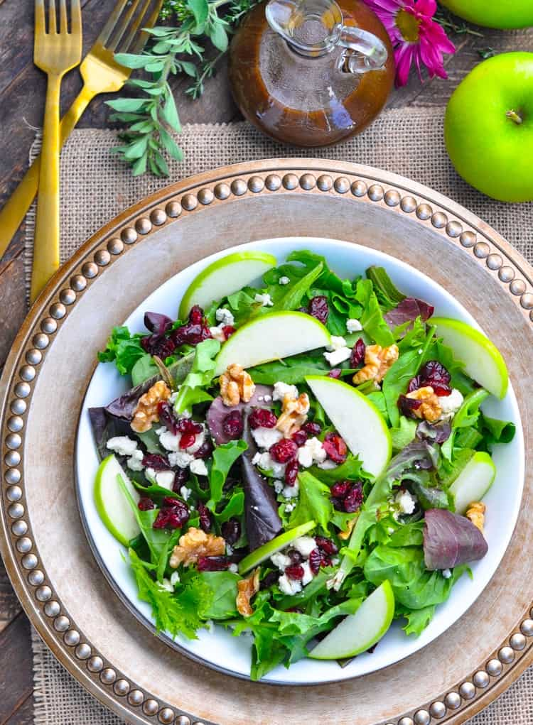 An overhead shot of a tossed salad with apple, cranberries, walnuts and cheese