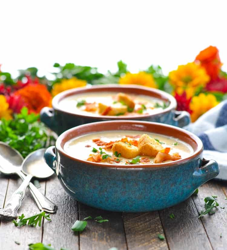 Two blue bowls of cheeseburger soup topped with croutons