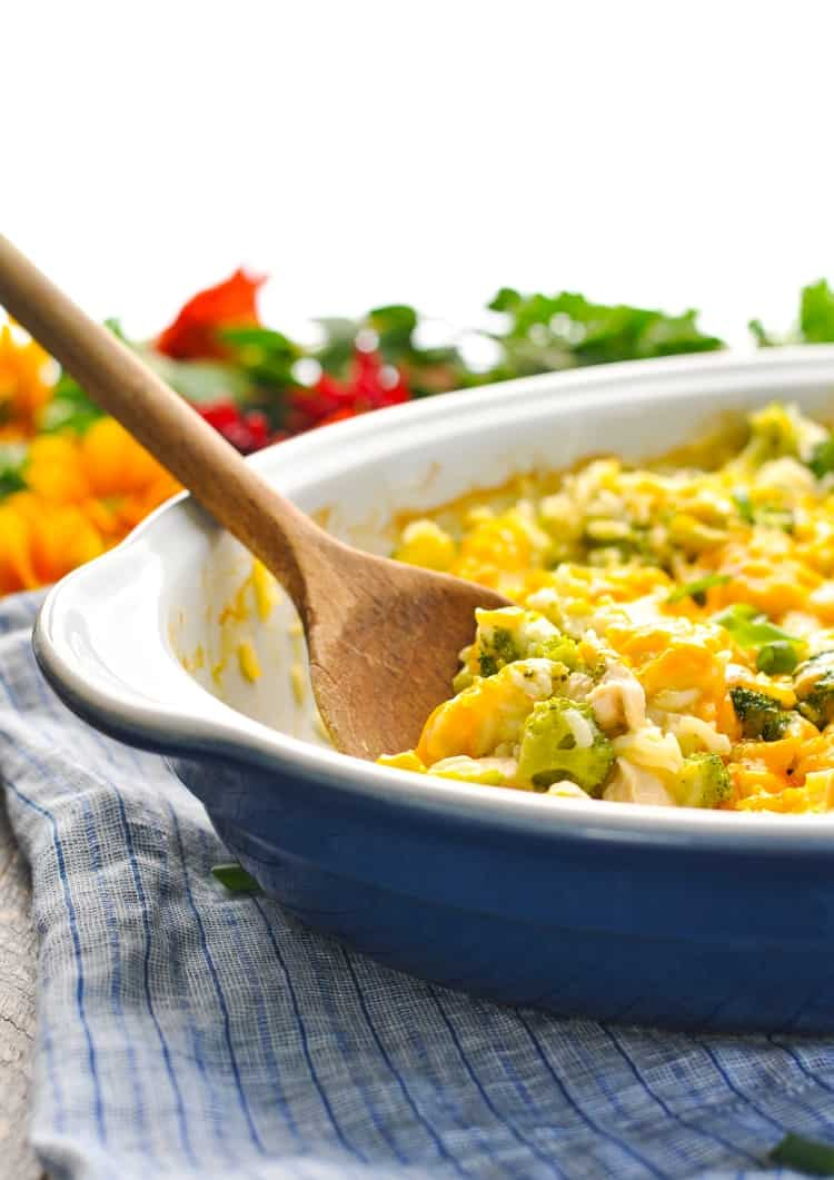An oval casserole dish with a chicken broccoli rice casserole inside and a wooden spoon