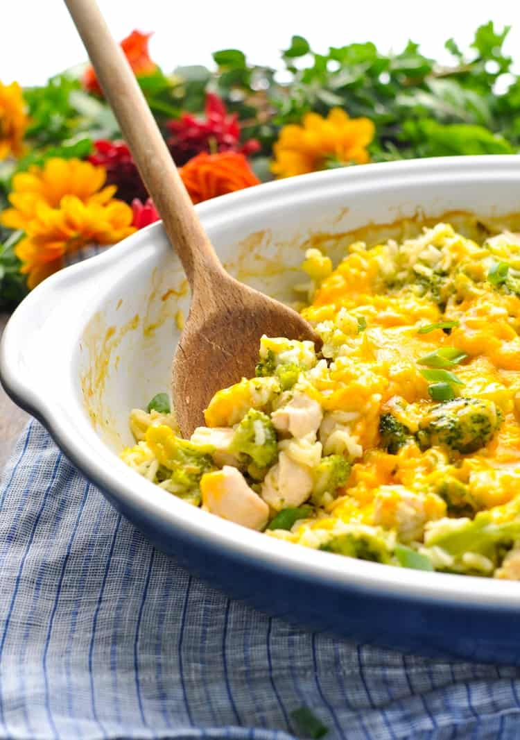 Side shot of a chicken broccoli rice casserole with a wooden spoon