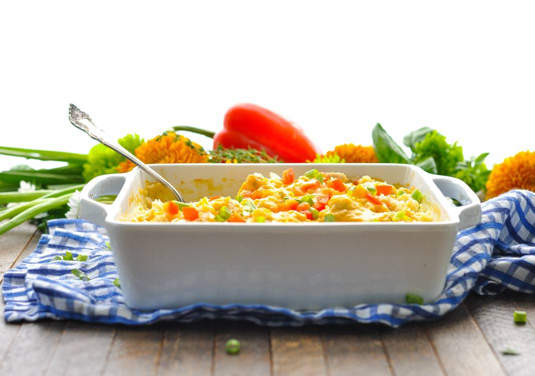 A white casserole dish filled with a fiesta chicken bake and a serving spoon at the side