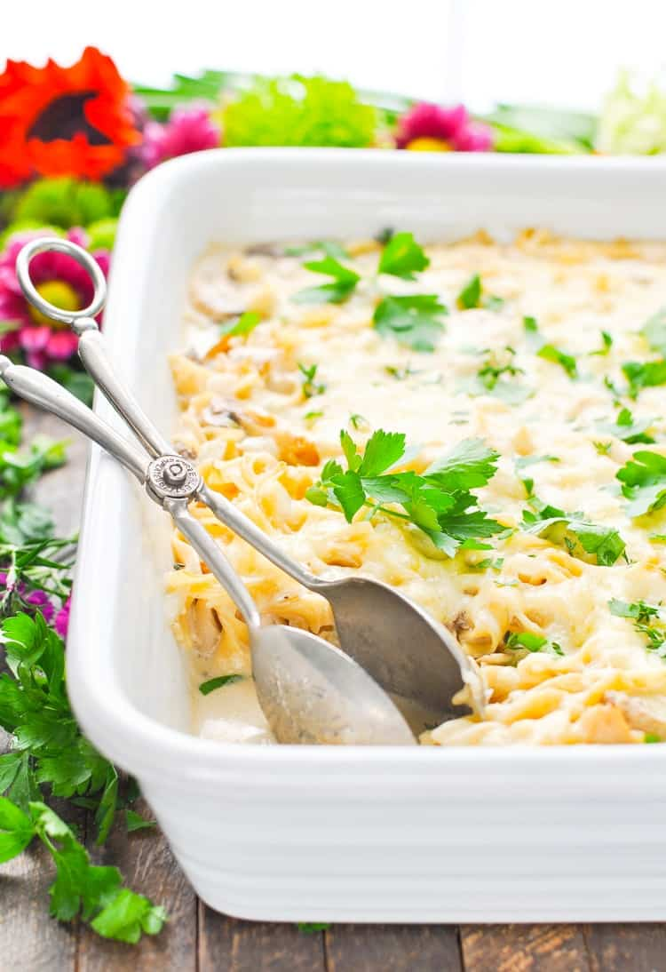 A white casserole dish with turkey tetrazzini and parsley on top
