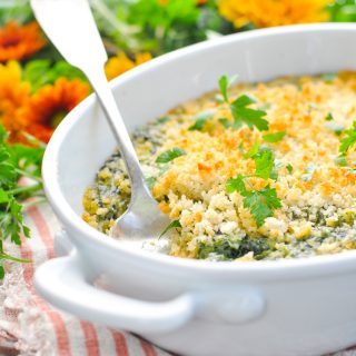Front shot of creamed spinach casserole in a white baking dish