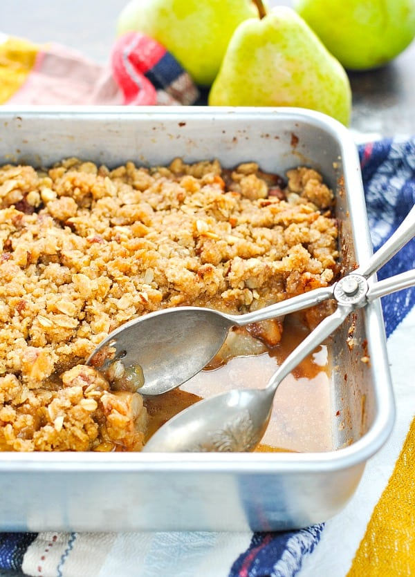 Front shot of pear crisp in a baking pan with serving tongs