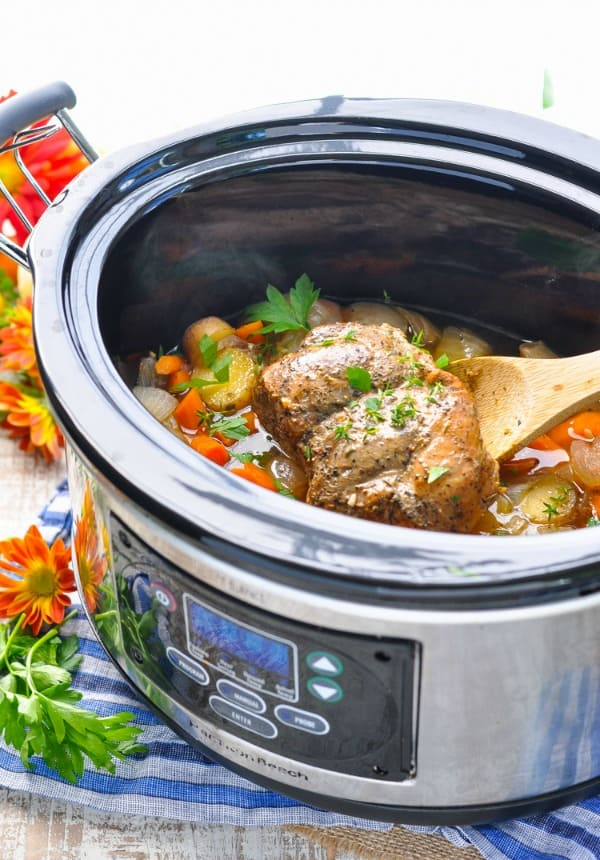 A side shot of slow cooker pork in a slow cooker with vegetables