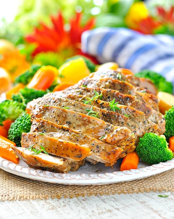 A close up of slow cooker pork cut into slices with vegetables on a plate
