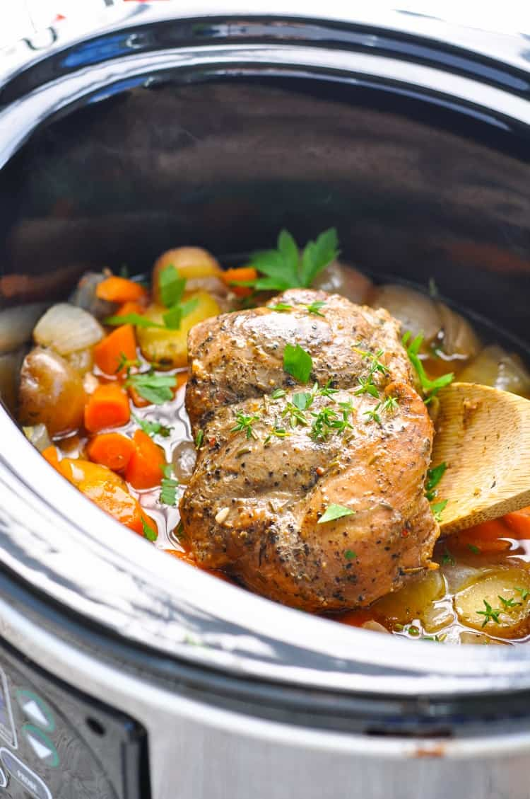 Slow cooker pork topped with fresh green herbs