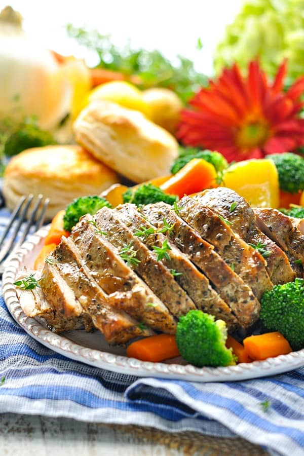 Sliced slow cooker pork loin roast surrounded by vegetables on a serving tray
