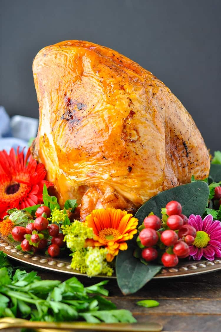 A roast turkey breast on a plate with garnishes