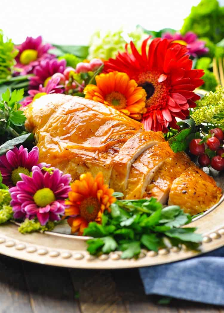 A sliced roast turkey breast on a plate with flowers
