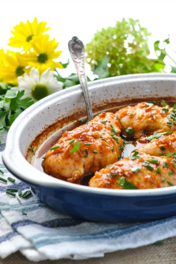 Honey French baked chicken breasts in a blue casserole dish with a serving spoon