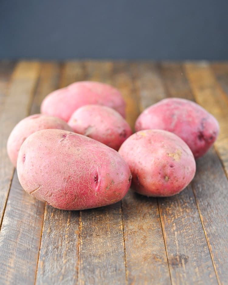 A pile of red potatoes on a wooden surface