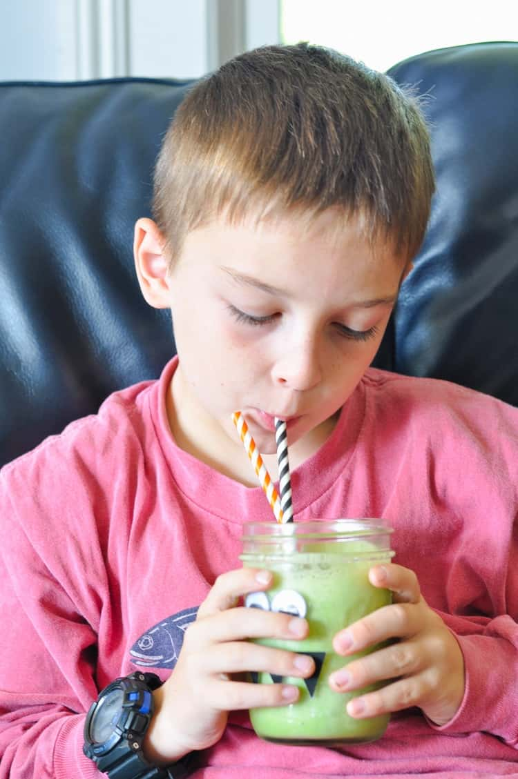 A boy holding a monster green smoothie with two hands and drinking it through a straw
