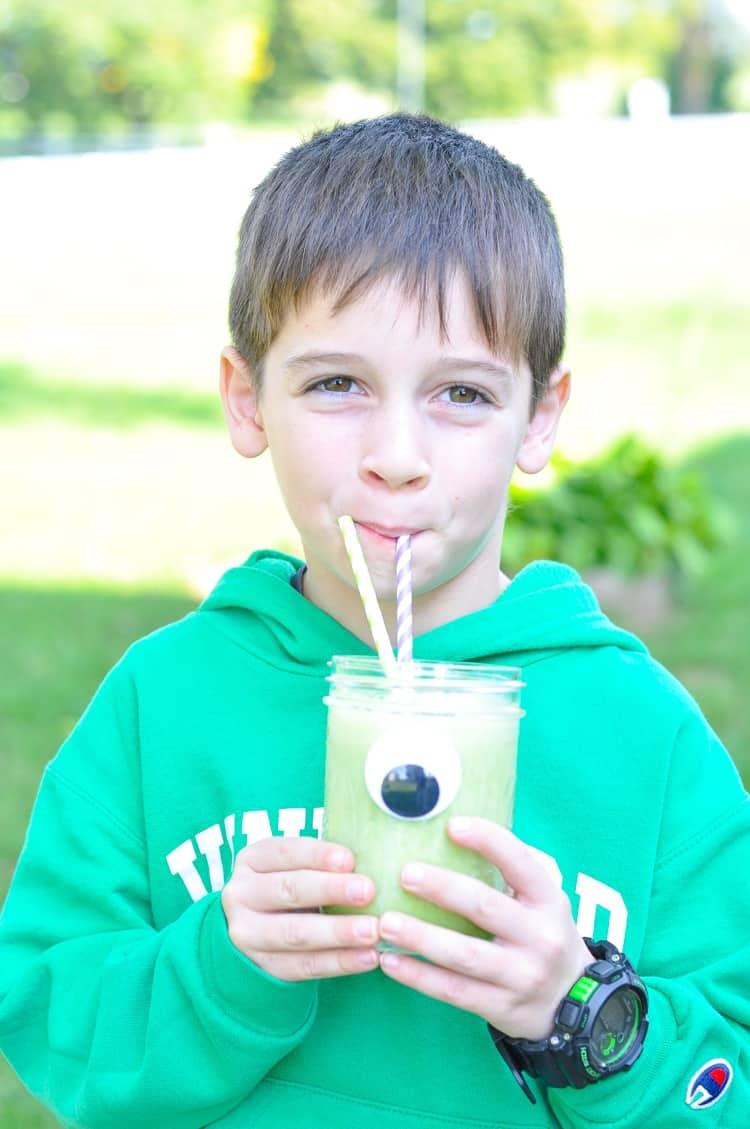 A boy drinking a monster green smoothie in a mason jar with two straws