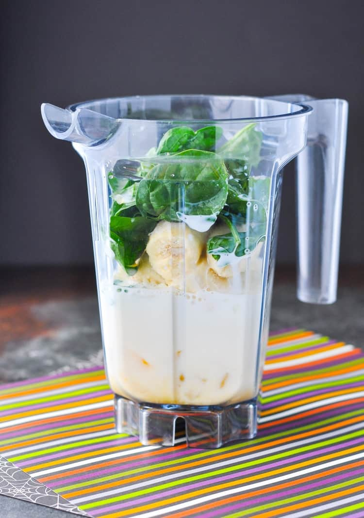 A blender jug filled with ingredients ready to make a monster green smoothie
