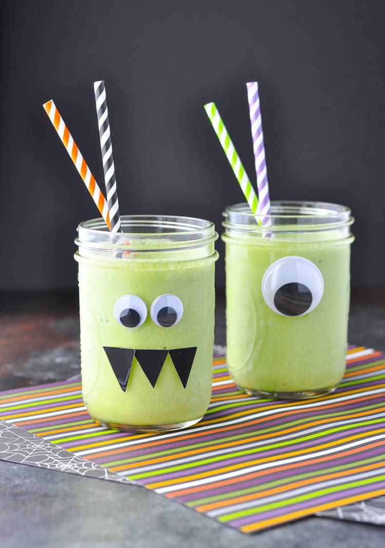 Two mason jars decorated with monster eyes and filled with a monster green smoothie