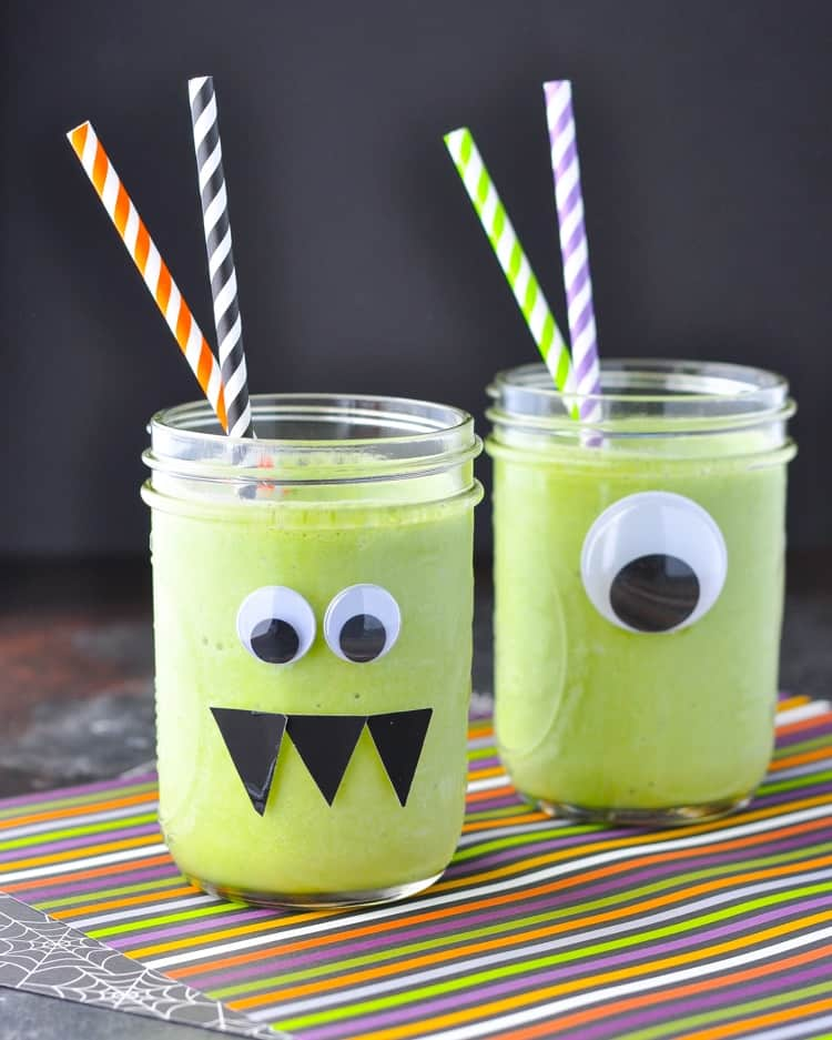 Two glass jars filled with a monster green smoothie and topped with colored straws