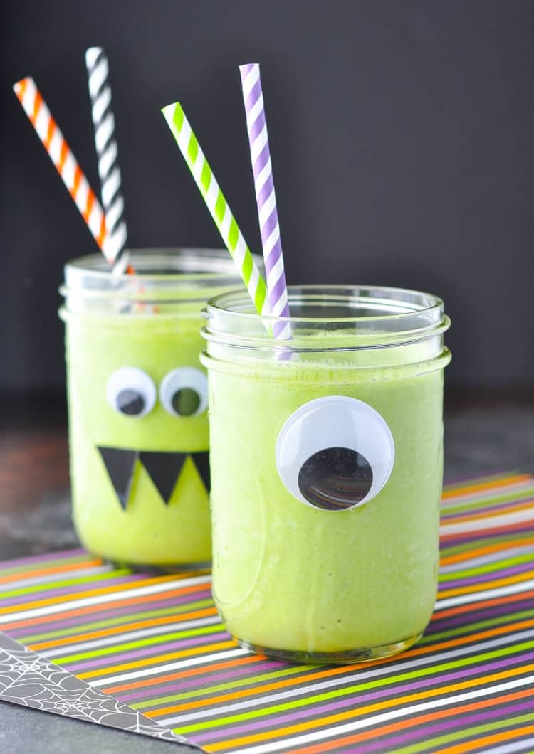 Two Mason jars filled with a monster green smoothie for kids decorated with monster eyes and colored straws