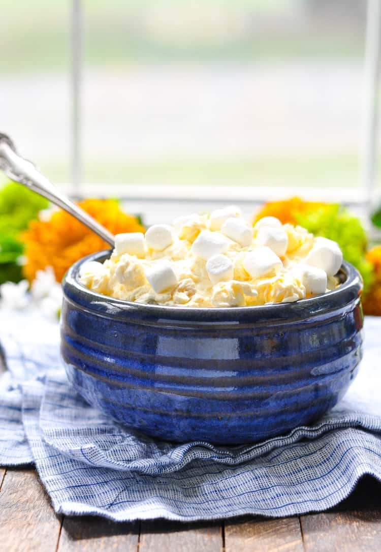 A side shot of orange pineapple fluff in a blue bowl with a silver spoon