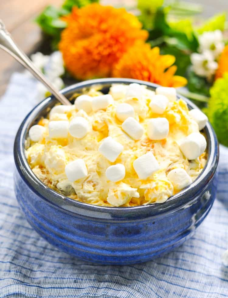A close up side shot of orange pineapple fluff in a blue bowl topped with marshmallows