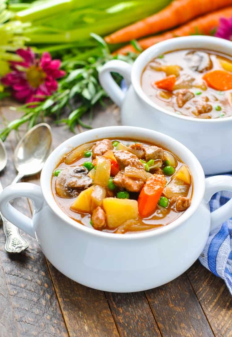 Slow cooker beef stew in a bowl topped with carrots and peas