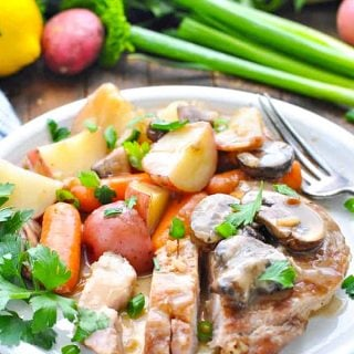 Front shot of slow cooker pork chops on a white plate with vegetables and gravy